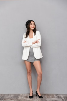 멀리보고, 회색 배경 위에 서있는 미니 스커트와 재킷을 입은 아름다운 젊은 여자의 전체 길이 초상화