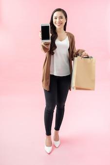 Полнометражный портрет красивой молодой женщины, стоящей изолированно на синем фоне, с сумками и показывающими черный экран мобильного телефона