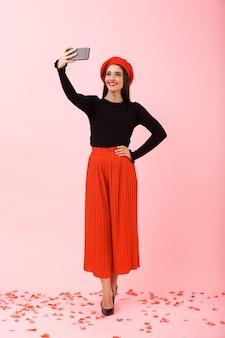 Полный портрет красивой молодой женщины в красном берете, стоящей изолированно на розовом фоне, делающей селфи