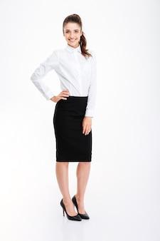 Полнометражный портрет деловой женщины, стоящей с рукой на бедре, изолированной на белой стене