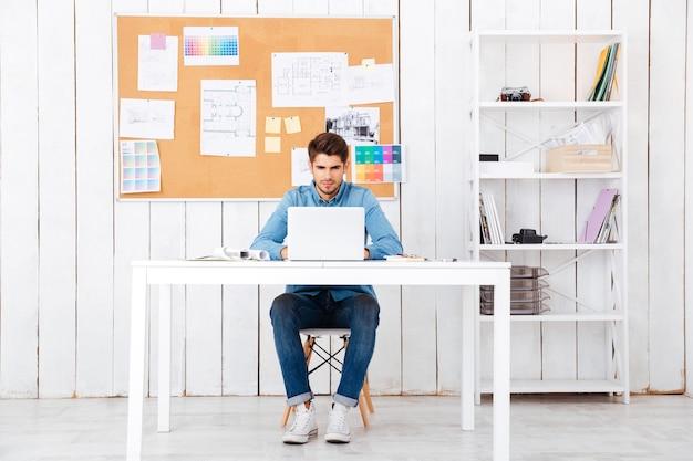 Портрет в полный рост случайного молодого человека с ноутбуком, сидящего за столом в офисе