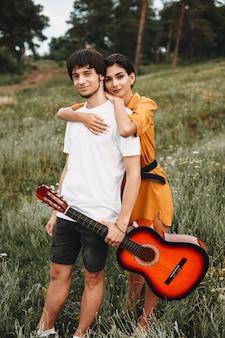 Полнометражный портрет очаровательной молодой пары, смотрящей в камеру, улыбаясь, пока девушка обнимает своего парня со спины на открытом воздухе в природе.