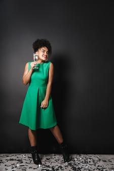 검은 벽 위에 서있는 드레스를 입고 쾌활한 아프리카 계 미국인 여자의 전체 길이 초상화