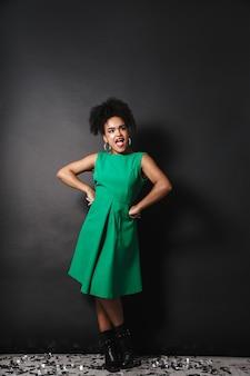 黒い壁の上に立っているドレスを着ている陽気なアフロアメリカ人女性の全身像