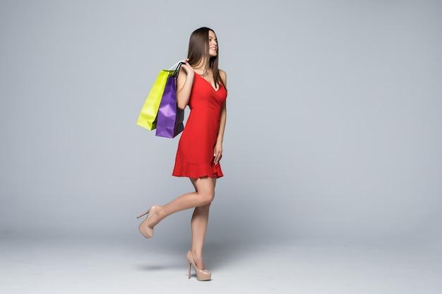 Портрет веселой привлекательной женщины в полный рост, держащей хозяйственную сумку, изолированную на белой стене