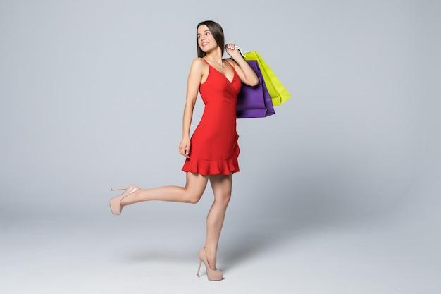 白い壁で隔離の買い物袋を保持している陽気な魅力的な女性の全身像