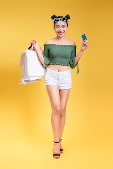 陽気な魅力的な女性の完全な長さの肖像画は、黄色の背景に買い物袋とクレジットカードを保持します。