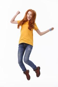 ジャンプする陽気なかわいい女性の全身像