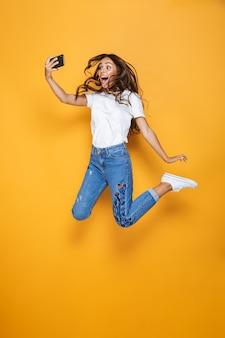 Портрет веселой девушки с длинными темными волосами в полный рост, перепрыгивающей через желтую стену и делающей селфи
