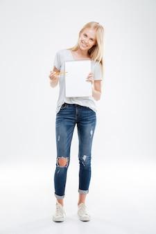 흰 벽에 격리된 빈 공책에서 연필을 가리키는 쾌활한 행복한 예쁜 소녀의 전체 길이 초상화