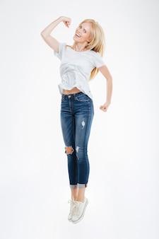 Портрет веселой счастливой женщины в полный рост, прыгающей на белом фоне