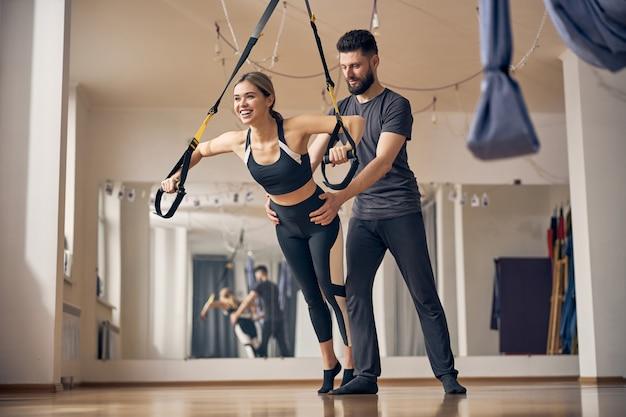 Портрет жизнерадостной дамы в полный рост, использующей тренажер подвески trx во время силовой тренировки