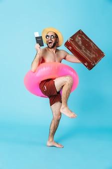 Портрет веселого человека без рубашки в полный рост в надувном кольце и солнцезащитных очках, с паспортом и изолированным чемоданом