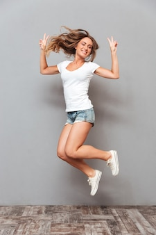 Портрет веселой женщины в полный рост, прыгающей и показывающей жест v изолирован на серой стене
