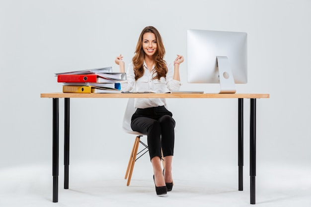 Полный портрет веселой женщины, сидящей за столом в офисе на белом фоне