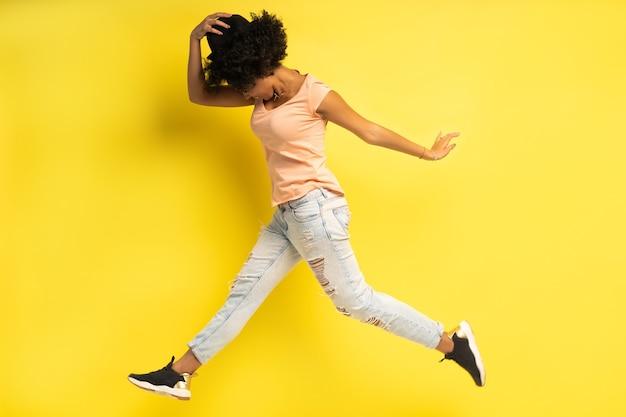 黄色の背景の上に孤立してジャンプしながら成功を祝う陽気な若いアフリカの女性の全身像。