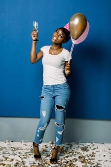 공기 풍선 및 푸른 공간을 통해 격리 샴페인 잔뜩 들고 쾌활 한 젊은 아프리카 여자의 전체 길이 초상화. 생일 파티, 축하 개념.