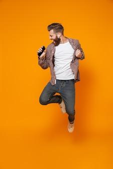 Портрет веселого молодого человека в повседневной одежде в полный рост, прыгающего под музыку в наушниках и держащего мобильный телефон