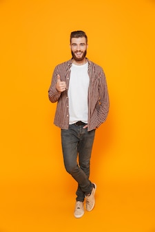 Портрет в полный рост веселого молодого человека в повседневной одежде показывает палец вверх