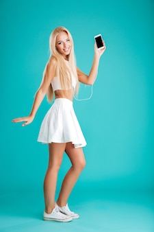 빈 화면 휴대 전화를 들고 파란색 벽에 고립 이어폰으로 음악을 듣고 쾌활한 젊은 여자의 전체 길이 초상화