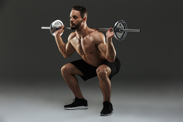 Полная длина портрет концентрированного без рубашки мускулистого спортсмена
