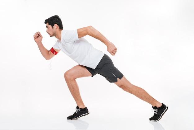 흰색 배경에 격리된 이어폰을 끼고 달리는 집중된 젊은 스포츠 남자의 전체 길이 초상화