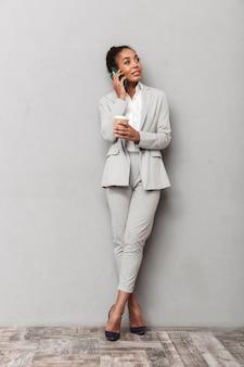 立っているスーツを着て、一杯のコーヒーを持って、携帯電話で話している自信を持ってアフリカのビジネス女性の完全な長さの肖像画