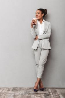 スーツを着て立って、持ち帰り用コーヒーのカップを保持している自信を持ってアフリカのビジネス女性の完全な長さの肖像画