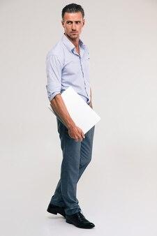 Полнометражный портрет уверенного бизнесмена, стоящего с ноутбуком и смотрящего на серое пространство