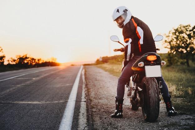 自信を持ってヨーロッパのバイカーが世界中をバイクで旅する準備をし、夕日を背景にカメラを見ている様子の全身像。