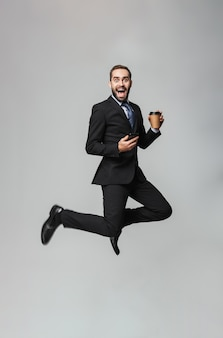 Полнометражный портрет уверенного в себе красивого бизнесмена в изолированном костюме, держащего кофе на вынос, использующего мобильный телефон, прыжки