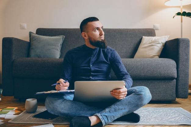 그의 다리에 노트북을 들고 노트북에 메모를하는 동안 멀리 찾고 바닥에 앉아 자신감 남성 프리랜서의 전체 길이 초상화.