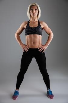 自信を持って筋肉の大人のスポーツウーマンの完全な長さの肖像画