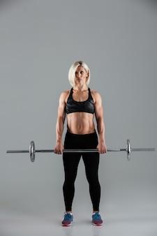 Полная длина портрет уверенной мускулистой взрослой женщины