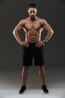 Полная длина портрет уверенно мускулистый мужчина позирует