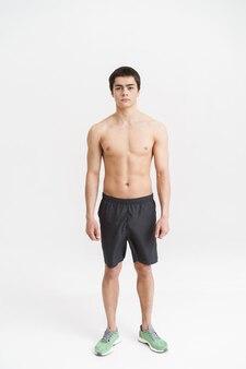 Полнометражный портрет уверенного спортсмена, стоящего над белой