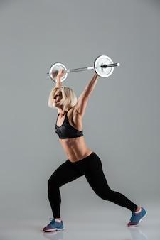 Полная длина портрет уверенной сильной мускулистой взрослой спортсменки
