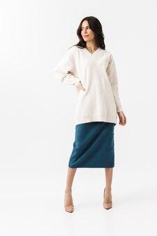 Портрет в полный рост уверенной в себе женщины, одетой в свитер и юбку, стоящую изолированную над белой