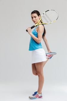 灰色の壁の上に孤立して立っているラケットとボールを保持している自信を持って女性テニスプレーヤーの完全な長さの肖像画