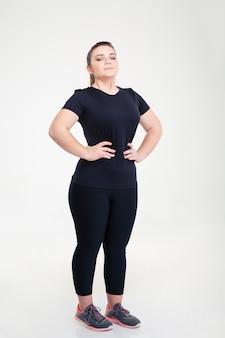 白い壁に隔離されて立っているスポーツウェアの太った女性の完全な長さの肖像画
