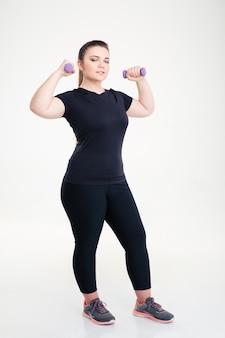 Портрет толстой женщины в спортивной одежде в полный рост с гантелями, изолированными на белой стене
