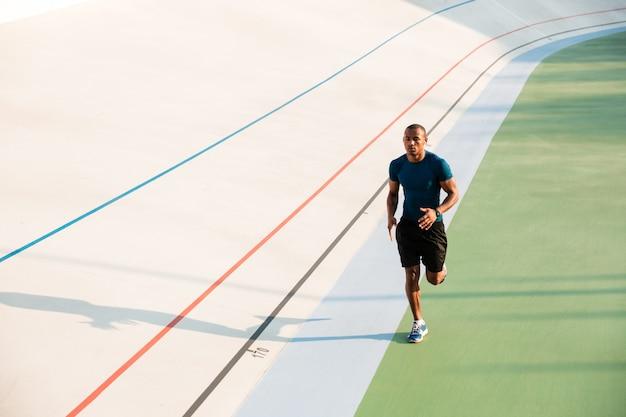 実行しているフィットの若いスポーツマンの完全な長さの肖像画