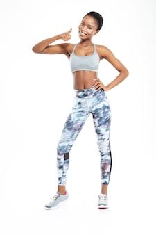 Портрет афро-американской женщины фитнеса в полный рост, показывая большой палец вверх, изолированные на белом фоне