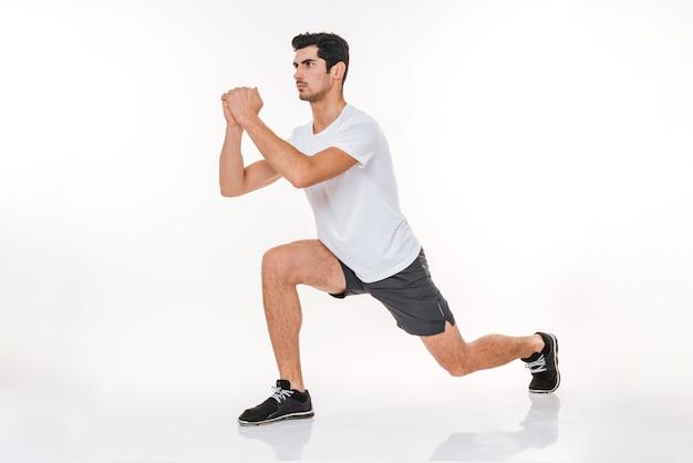 Полнометражный портрет фитнес-мужчины, делающего приседания, изолированные на белой стене