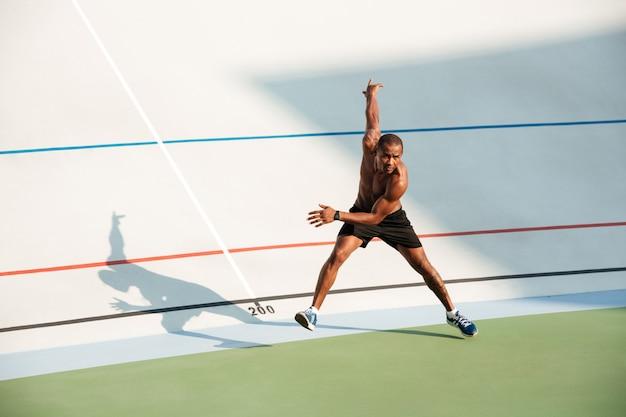 반 벌거 벗은 근육 운동가의 전체 길이 초상화