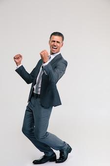Полнометражный портрет красивого бизнесмена, празднующего свою победу изолирован