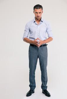 Полный портрет красивого бизнесмена, стоящего над серым пространством