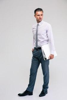 Полный портрет красивого бизнесмена, стоящего с изолированной папкой