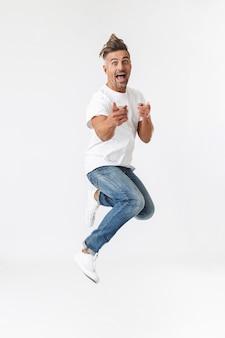 Полнометражный портрет красивого случайного человека, прыгающего изолированно на белом, празднует успех