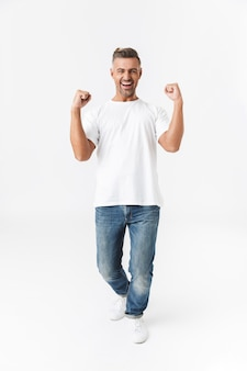 Полнометражный портрет красивого случайного человека, стоящего изолированно на белом и празднующего успех